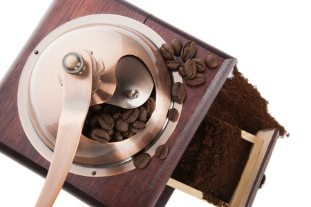 Coffee mill with coffee beans and ground coffee isolated on white background, top view. Aromatic coffee background. photo