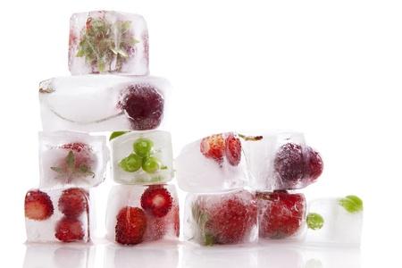 Färska frukter och grönsaker frysta i isbitar isolerad på vit bakgrund. Ny sund sommar äta.