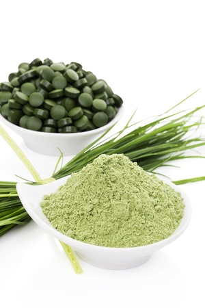 Green food supplement. Spirulina, chlorella and wheatgrass. Green pills, wheatgrass blades and ground powder isolated on white background. Healthy lifestyle. Stock Photo