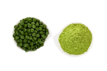 Green food supplement. Spirulina pills and wheatgrass ground. Green pills and ground powder isolated on white background, top view. Healthy lifestyle.