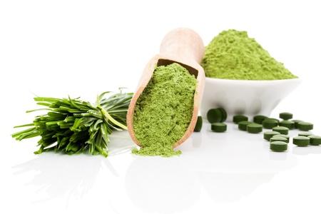 Spirulina, chlorella en tarwegras. Groen voedingssupplement. Groene pillen, tarwegras bladen en gemalen poeder op een witte achtergrond. Gezonde levensstijl.