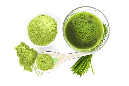 Groen voedingssupplement. Spirulina, chlorella en tarwegras. Groene pillen, tarwegras bladen en gemalen poeder op een witte achtergrond, bovenaanzicht. Gezonde levensstijl. Stockfoto
