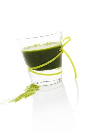 Gezond leven. Spirulina, chlorella en tarwegras. Glas met groene drankje en tarwegras gemalen op een witte achtergrond. Voedingssupplement. Stockfoto