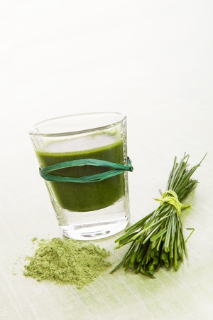 Green food supplement. Spirulina, chlorella and wheatgrass. Green drink, wheatgrass blades and ground powder isolated on white background. Healthy lifestyle. photo