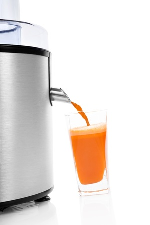 Fresh carrot juice in glass and silver electric juicer isolated on white background with reflection. Healthy lifestyle, minimal sparse contemporary styles. photo