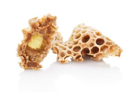 Bidrottninggelé i honungskaka isolerad på vit bakgrund. Skönhet och antiaging koncept. Organiska och naturkosmetika.