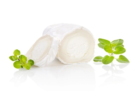 Slices goat cheese and goat cheese piece with fresh marjoram herbs isolated on white background. Culinary cheese eating.