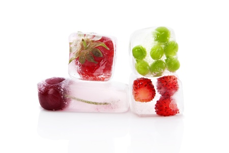 Fresh berry fruits and green peas frozen in ice cubes isolated on white background. Fresh summer healthy eating.