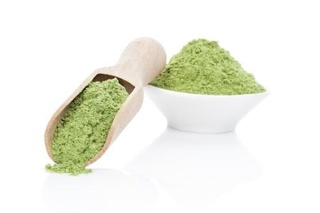 나무 국자에와 그릇에 지상 밀 잔디 분말 흰색 배경에 고립입니다. 건강한 라이프 스타일. 녹색 식품 보충제. 스톡 콘텐츠