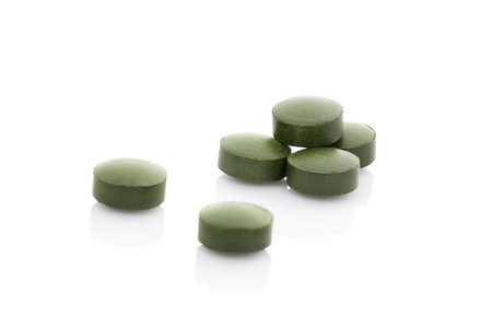 spirulina: Chlorella, spirulina and wheatgrass. Green pills isolated on white background. Healthy lifestyle, natural organic nutritional supplement. Stock Photo
