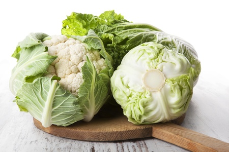 Cabbage, chinese cabbage and cauliflower on wooden cutting board on white textured wooden background. Healthy summer vegetable, country style. photo
