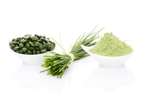 Wheatgrass in powder, wheat grass blades, spirulina and chlorella pills isolated on white background. Healthy living.