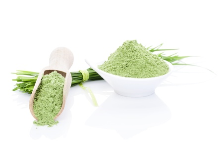 Luxurious wheat grass still life. Ground wheat grass powder on wooden scoop and fresh blades isolated on white background. Healthy lifestyle.  photo