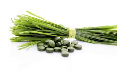 Tarwegras bladen en groene pillen op een witte achtergrond. Organische natuurlijke gezond voedingssupplement. Superfood.