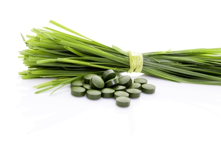 Wheatgrass blades and green pills isolated on white background. Organic natural healthy food supplement. Superfood.