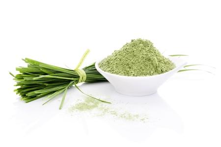 Barley Grass en Tarwegras. Bladen en poeder op een witte achtergrond. Groen voedsel. Natuurlijke organische gezond leven. Stockfoto