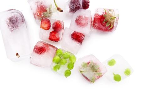 Verse rijpe zomer fruit en groente bevroren in ijsblokjes op een witte achtergrond met reflectie. Gezonde zomer eten.