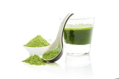 숟가락에 밀 잔디 분말, 반사 자연 유기 건강한 라이프 스타일 흰색 배경에 고립 된 유리에 녹색 보리 잔디 주스