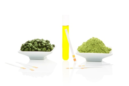 acidic: Urine sample in test tube, pH test strips, green pills and green ground powder isolated on white background  Wheatgrass, chlorella, spirulina  Acidic or alkaline, healthy or sick