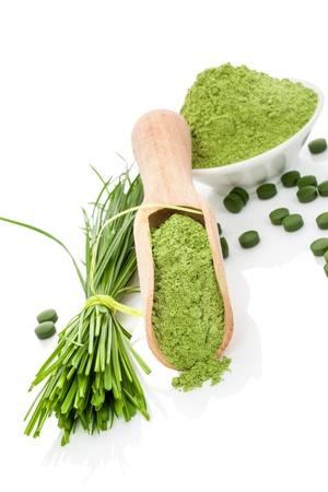 Natuurlijke kruiden organische alternatieve geneeskunde Superfood Tarwegras poeder, messen en groene pillen op houten lepel en witte kom geïsoleerd op wit Gezonde leefstijl Stockfoto