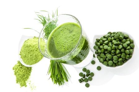 Natuurlijke superfood Alternatieve geneeswijzen Detox Ground tarwegras, gerst gras bladen, chlorella pillen en spirulina groene sap geïsoleerd op witte achtergrond Gezond leven