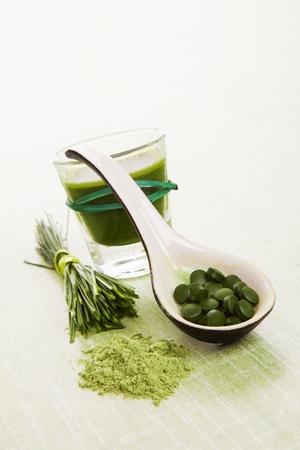 Wheat grass, barley grass, chlorella, spirulina  Herbal natural food supplements  Ground powder, pills on spoon and green juice