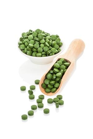 그릇과 나무 국자에 녹색 약. 천연 허브 대체 의학. 클로렐라, 스피루리나, 밀 잔디와 보리 잔디. 건강한 삶.