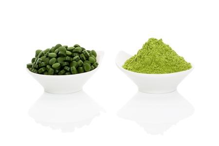 Tarwegras poeder en groene chlorella pillen in twee kommen geïsoleerd op een witte achtergrond. Alternatieve kruidengeneeskunde. Gezond leven Stockfoto