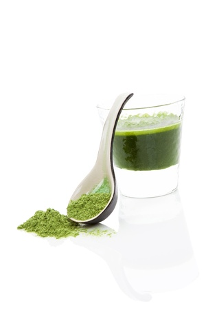 Green wheatgrass, spirulina and chlorella juice in glass isolated on white background with wheat grass powder on ceramic spoon. Healthy detox concept.