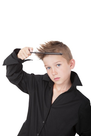 Charming young casual boy with cool haircut, holding hairbrush isolated on white background. Man fashion concept. photo