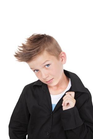 Charmante ongedwongen kind in zwarte jurk shirt en modieus kapsel met koele houding geïsoleerd op een witte achtergrond.