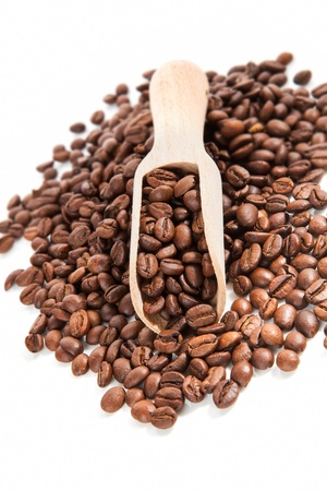 Pile of coffee beans and coffee beans on wooden scoop isolated on white background. Traditional coffee background. photo