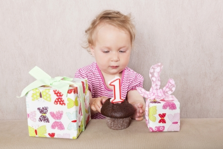 First birthday. Charming caucasian baby girl with presents and birthday cake on beige background.  photo