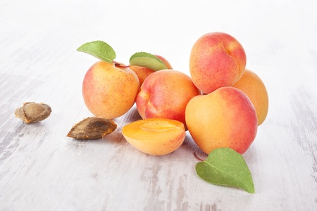 apricot kernels: Fresh apricots on white wooden background. Healthy summer fruit eating.