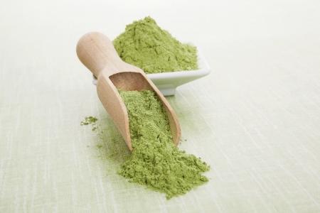 Groene superfood. Tarwegras grond op houten lepel en kom op groene achtergrond. Gezond eten en detox.
