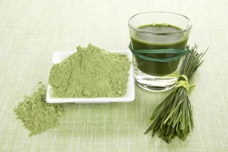 녹색 식품 보조제. 녹색 주스, 밀 잔디 분말 및 녹색 배경에 보리 잔디 블레이드. 해독과 건강한 생활. 스톡 콘텐츠
