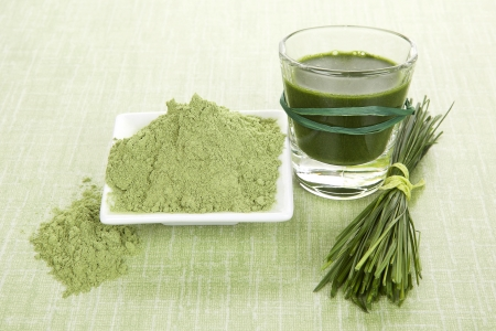 Green food supplements. Green juice, wheat grass powder and barley grass blades on green background. Detox and healthy living.