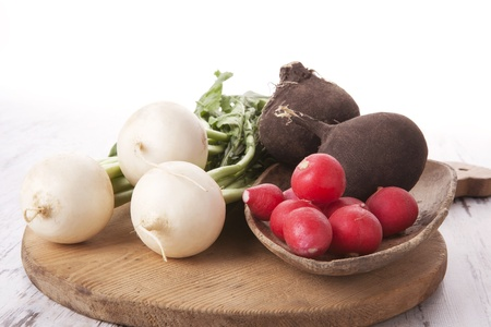Black, white and red radish on wooden kitchen board on white wooden background. photo