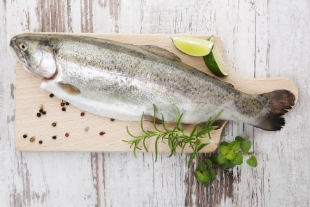 Fresh trout with pepper corns, fresh herbs and lemon on wooden kitchen board on white wooden background ready for grill. Delicious grilling concept. photo