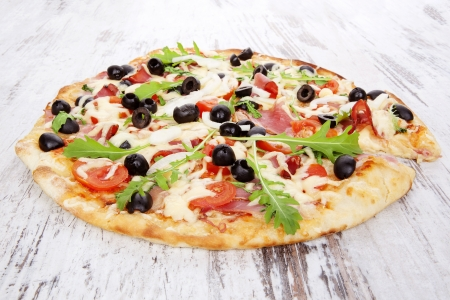 gourmet dinner: Delicious pizza with ham, black olives, fresh herbs and melted cheese on white wooden background. Traditional rustic style pizza eating.