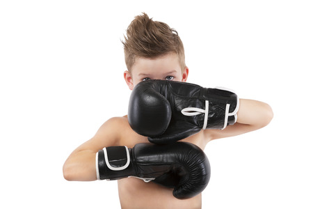 Charming boy with boxing gloves protecting his face isolated on white background. Sport and fitness. photo