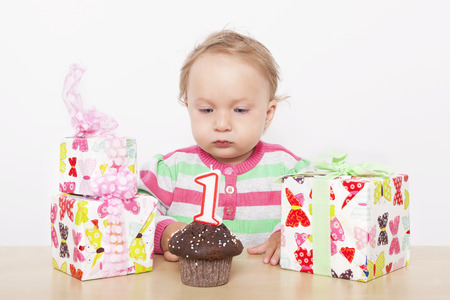 First birthday. Cute baby girl with birthday cake and birthday presents.  photo