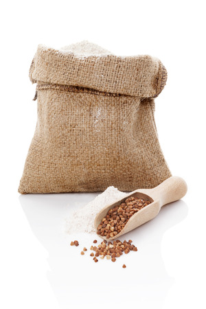 Flour in brown bag and buckwheat in wooden scoop isolated on white background.  photo