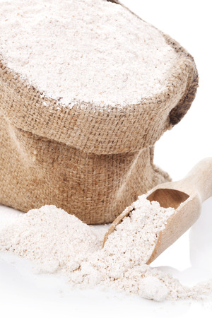 wooden scoop: Flour in brown sack and on wooden scoop isolated on white background.
