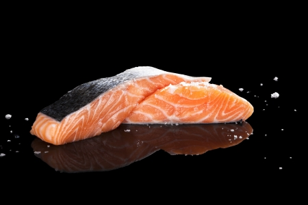 Raw salmon piece with sea salt crystals isolated on black background  Culinary seafood eating  photo
