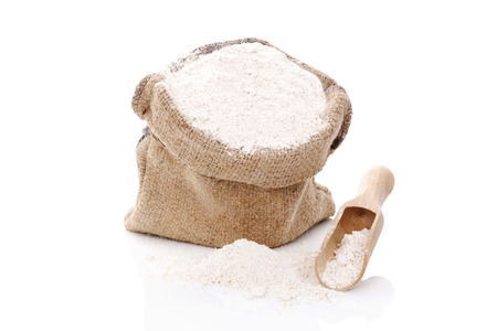 White flour in brown burlap bag with wooden scoop isolated on white background. Archivio Fotografico
