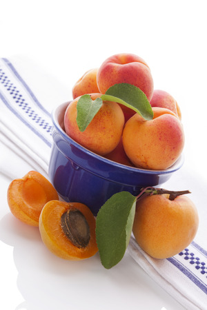 apricot kernels: Fresh apricots on white and blue table cloth on white background. Healthy summer fruit eating.  Stock Photo
