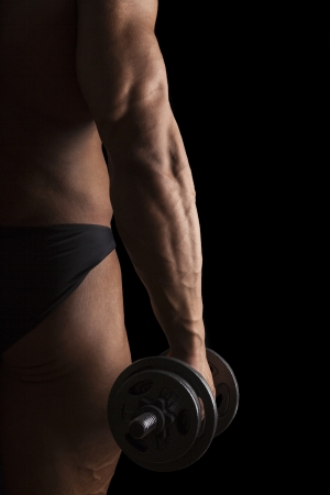 Sport and Fitness. Sexy bodybuilder holding dumbbell isolated on black background. photo