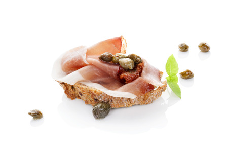 Luxurious canape background. Ciabatta slice with prosciutto, dry tomato and capers isolated on white background. Culinary eating. photo