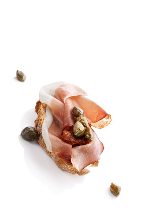 Delicious canape with prosciutto, capers and dry tomatoes isolated over white. Culinary eating. photo